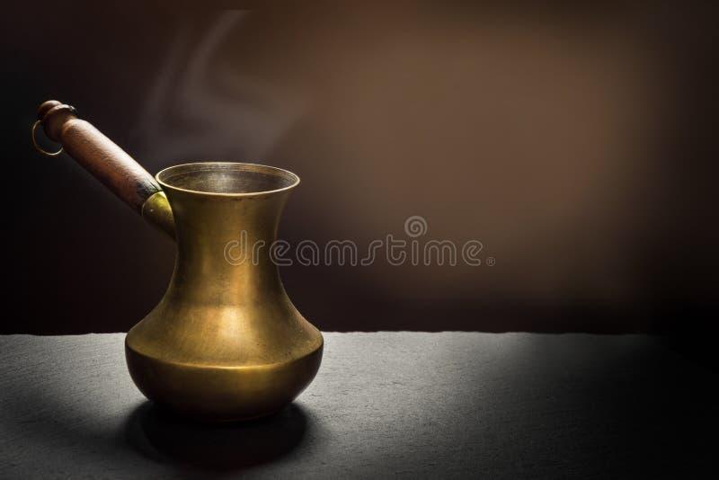 Caffè nero nel vecchio cezve di rame sull'ardesia nera come fondo con lo spazio della copia fotografia stock
