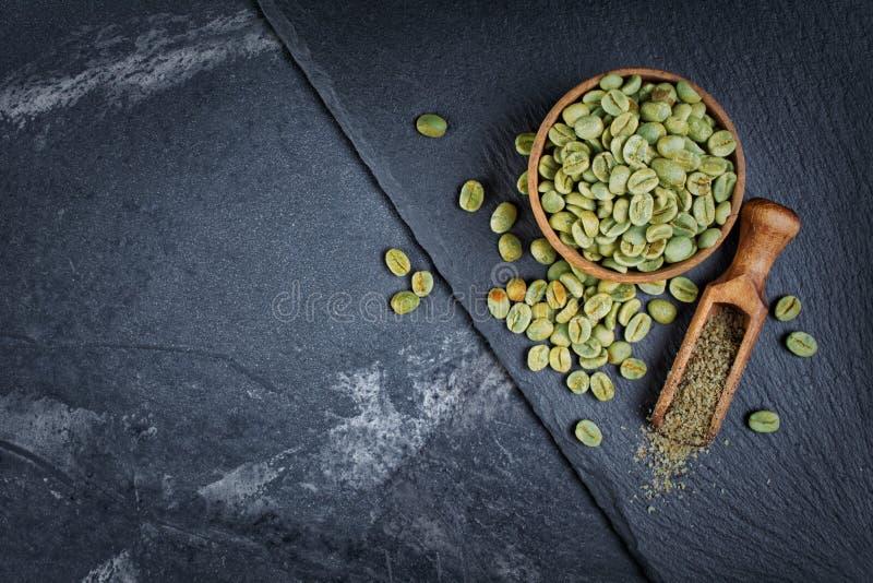 Caffè non arrostito verde crudo in ciotola di legno con i fagioli a terra in mestolo di legno sul bordo nero dell'ardesia fotografia stock