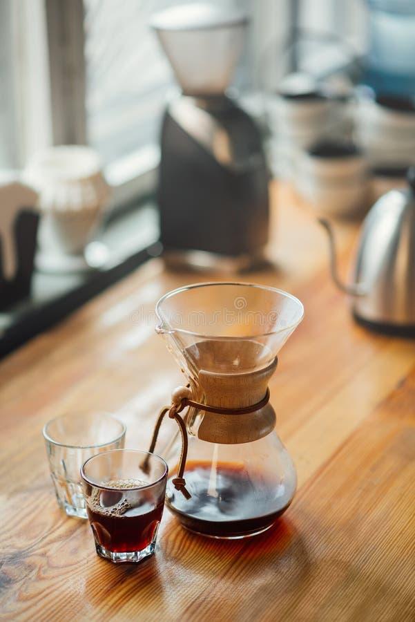 Caffè preparato secondo un metodo alternativo su una tavola in vetro sfaccettato e in una brocca trasparente fotografia stock