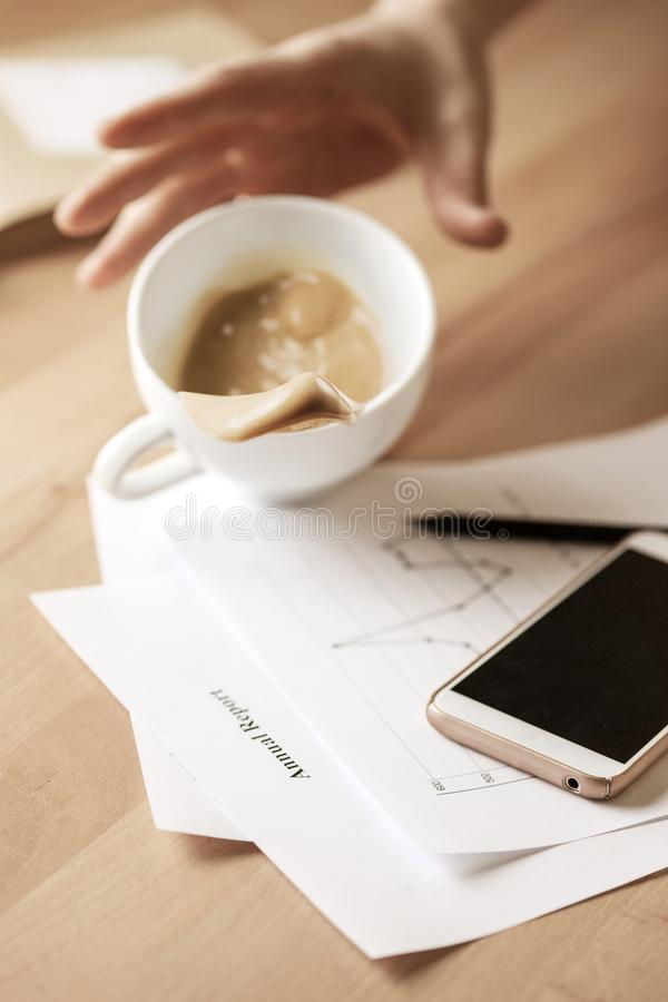 Caffè in tazza bianca che si rovescia il giorno lavorativo della tavola di mattina alla tavola dell'ufficio fotografia stock libera da diritti