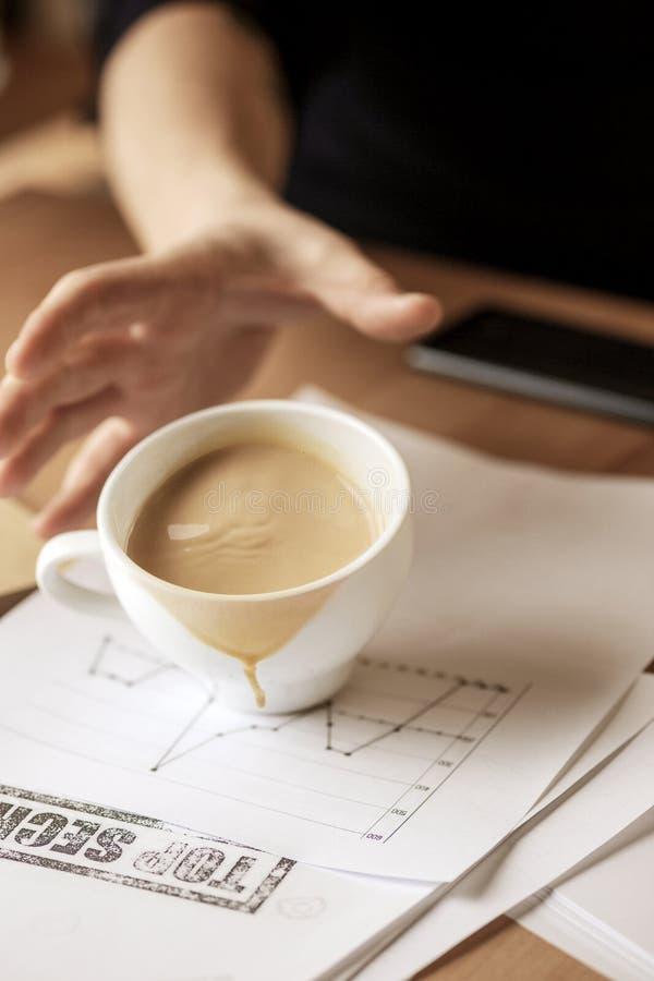 Caffè in tazza bianca che si rovescia il giorno lavorativo della tavola di mattina alla tavola dell'ufficio fotografia stock