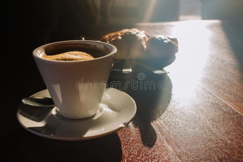 Caffè in tazza e croissant bianchi sulla tavola di legno alla luce solare di mattina Concetto del caffè dell'aroma di mattina Taz fotografie stock libere da diritti