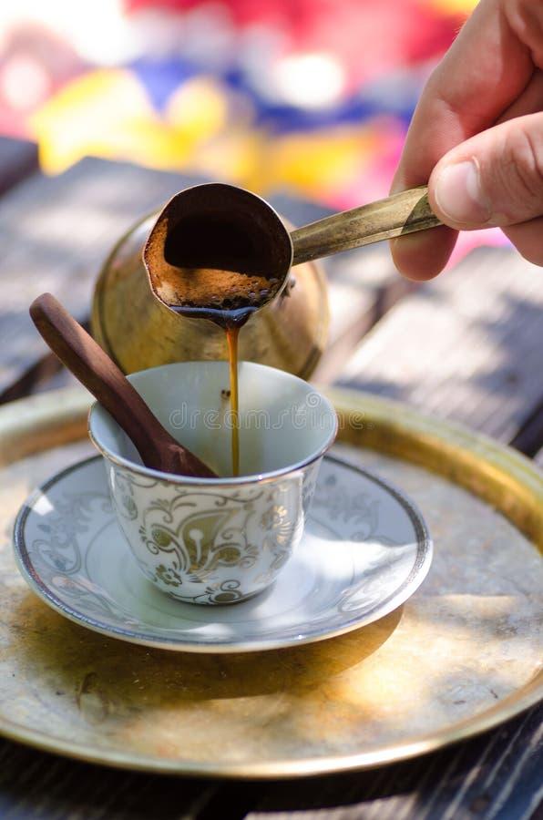 Caffè turco di versamento dal vaso tradizionale del metallo immagini stock libere da diritti