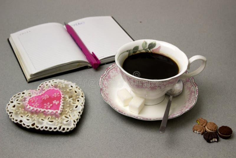 Caffè in una tazza accanto ad un pan di zenzero sotto forma di un cuore fotografie stock libere da diritti