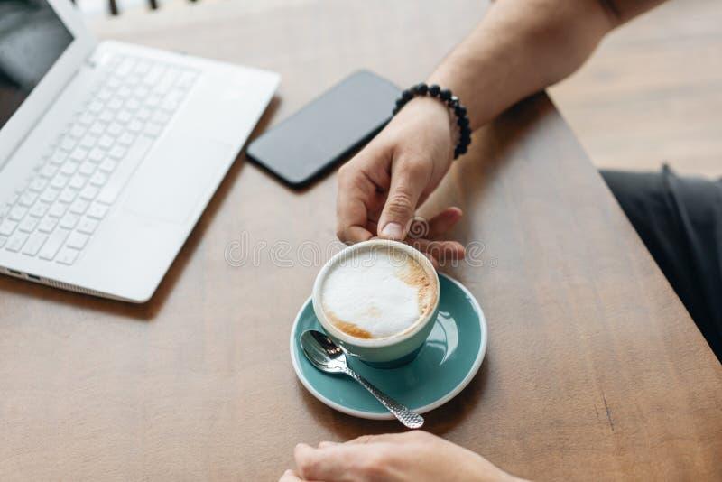 Caff? bevente del giovane da una tazza Lavoro delle free lance su netbook nel coworking moderno Programmatore al lavoro a distanz fotografie stock libere da diritti