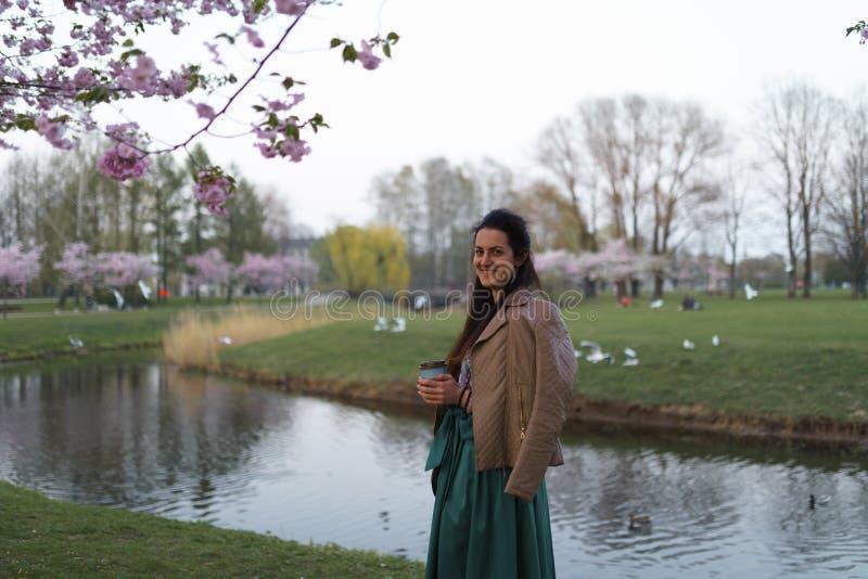 Caff? bevente della giovane donna da una tazza di carta che porta la gonna verde smeraldo di colore - fiore di ciliegia variopint immagine stock