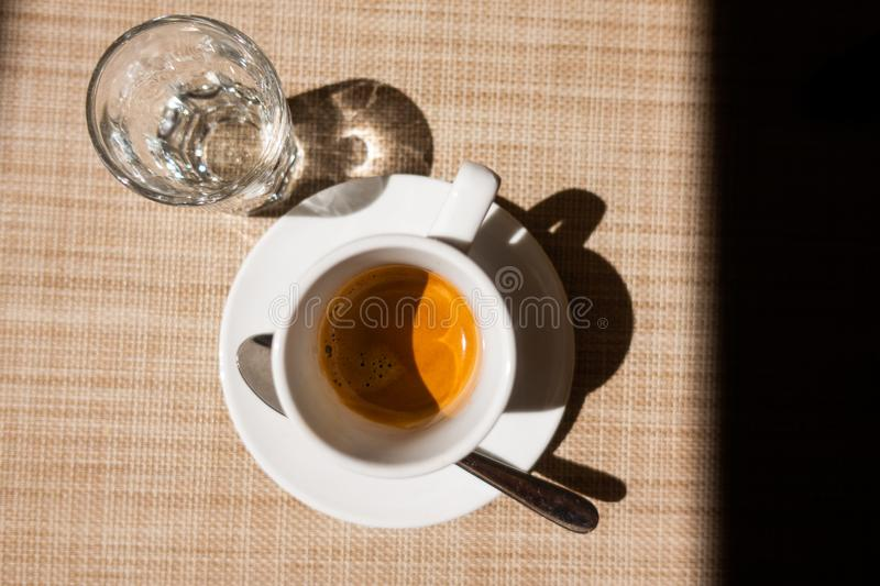 Caffe corretto, traditional Italian beverage with espresso and a shot of liquor, usually grappa. Top view on beige background and dark frame to right stock image