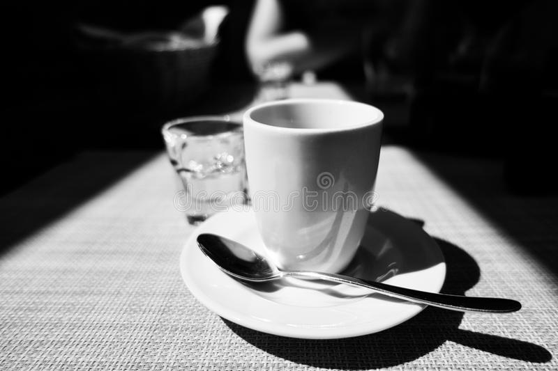 Caffe corretto, traditional Italian beverage with espresso and a shot of liquor, usually grappa, black and white. Caffe corretto, traditional Italian beverage royalty free stock image