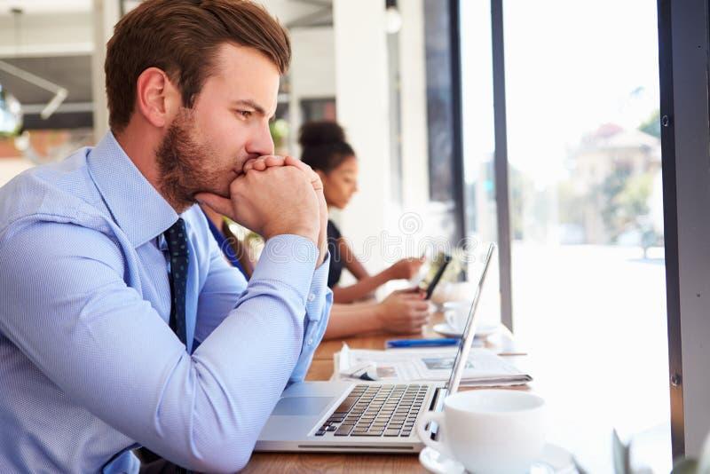 Caffetteria di Using Laptop In dell'uomo d'affari immagine stock libera da diritti