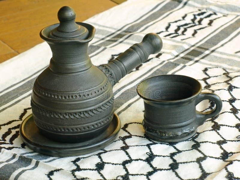 Caffettiera e tazza ceramiche su una sciarpa bianca del keffiyah immagini stock