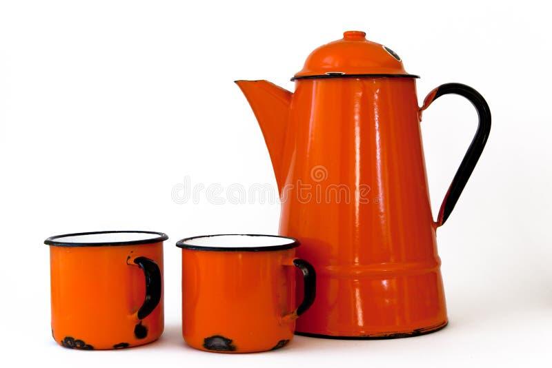 Caffettiera e tazze arancio fotografie stock