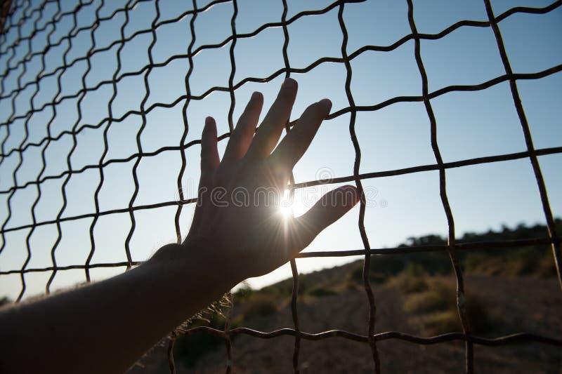Cage émouvante de barrière de main humaine en prison et immigration illégale sur le coucher du soleil photos stock