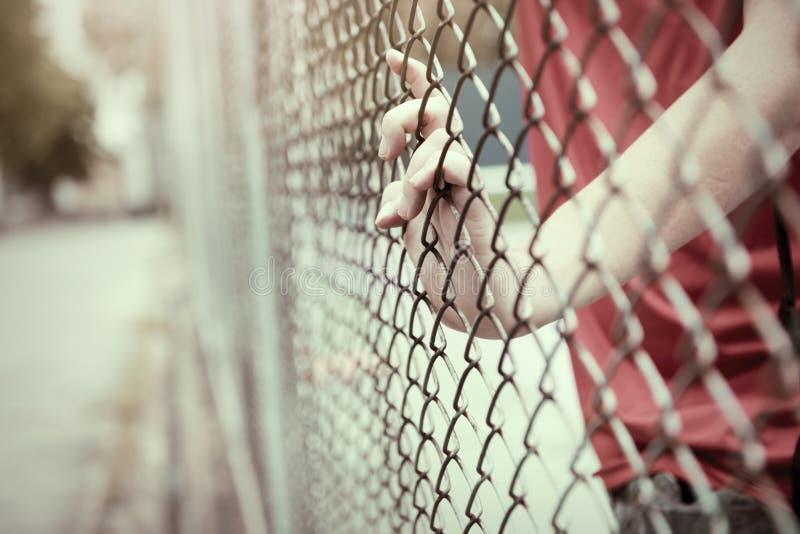 Cage contagieuse de maille de main Le prisonnier veulent la liberté image stock