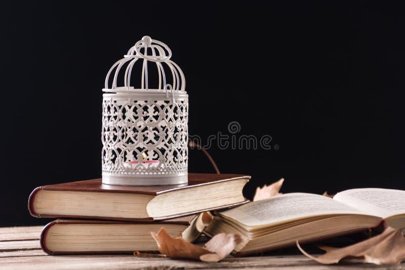 Cage décorative avec la bougie brûlant sur des livres sur le rétro bureau en bois photo libre de droits