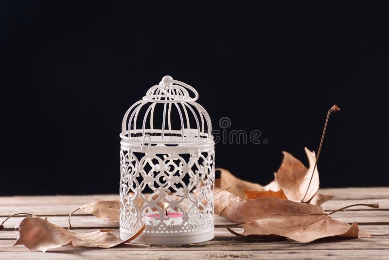Cage décorative avec la bougie brûlant sur le rétro bureau en bois images libres de droits