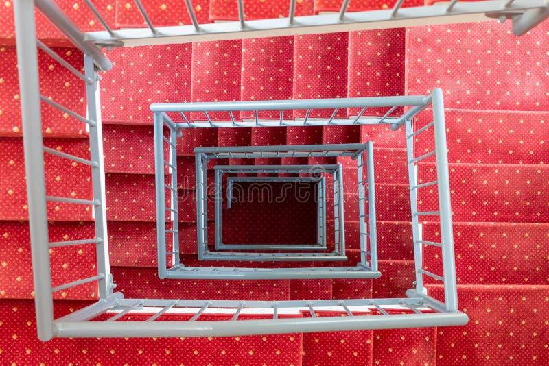 Cage d'escalier symétrique de vue supérieure avec le tapis rouge et le parapet en acier photos libres de droits