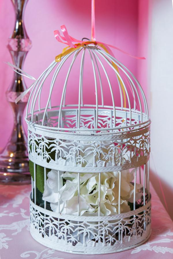 Candy Bar. The cage with flowers stand in restaurant . white roses put on the top of bird cage royalty free stock image