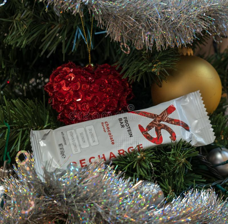 CAGLIARI ITALIEN - DECEMBER 2018: Stång för protein för XS-sportnäring på ett julträd Naturliga Nutrilite och strikt vegetarianti royaltyfria foton
