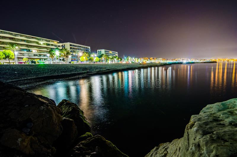Cagnes sur Mer, Frankrijk - Juni 20, 2018 Nachtfoto van stad op de kust met bezinning stock foto