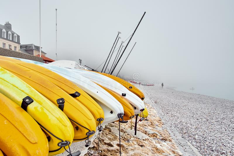 Caiaque amarelos em um Pebble Beach rochoso no amanhecer com névoa nevoenta no fundo foto de stock