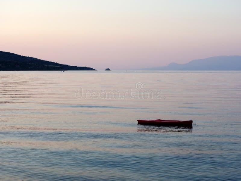 Caiaque do mar amarrado na baía, alvorecer fotografia de stock