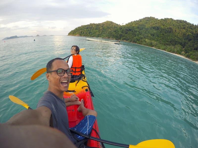 Caiaque do mar da navigação do homem e da mulher sobre a água clara da ilha imagens de stock
