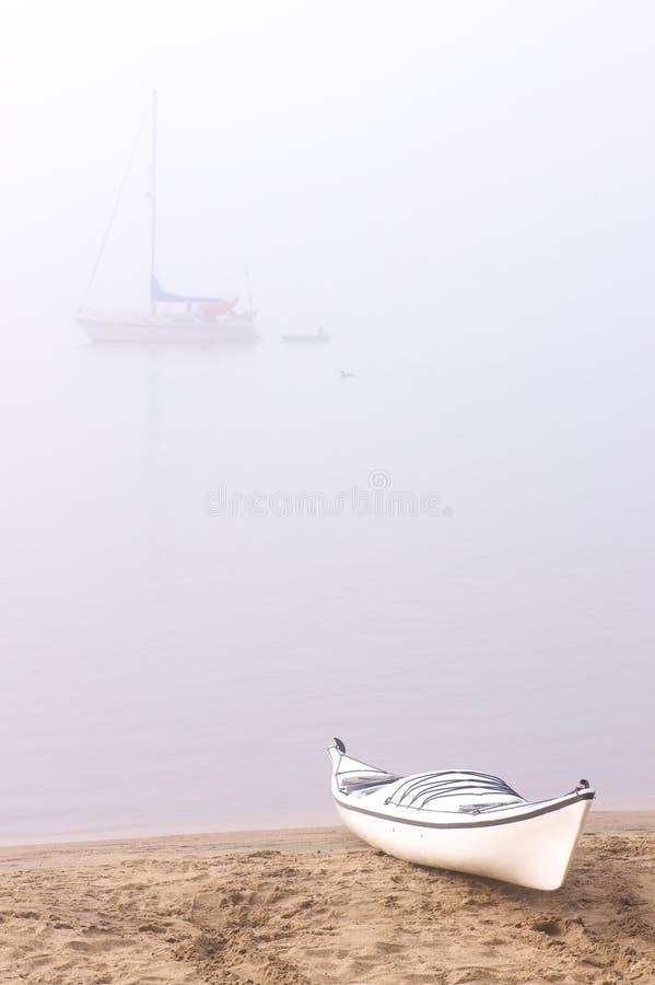 Caiaque na praia nevoenta foto de stock