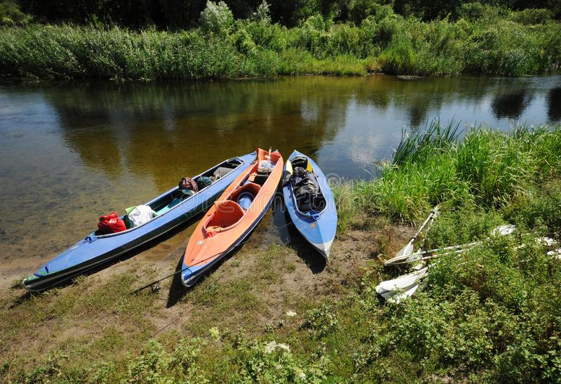 3 caiaque no banco de um rio pequeno no verão fotos de stock royalty free