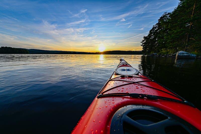 Caiaque plástico vermelho na água calma no por do sol imagens de stock royalty free
