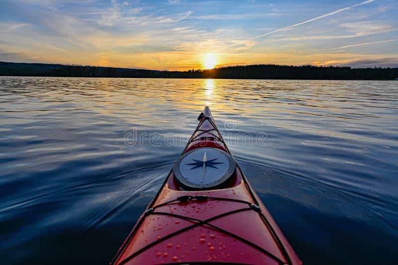 Caiaque plástico vermelho na água calma no por do sol fotografia de stock