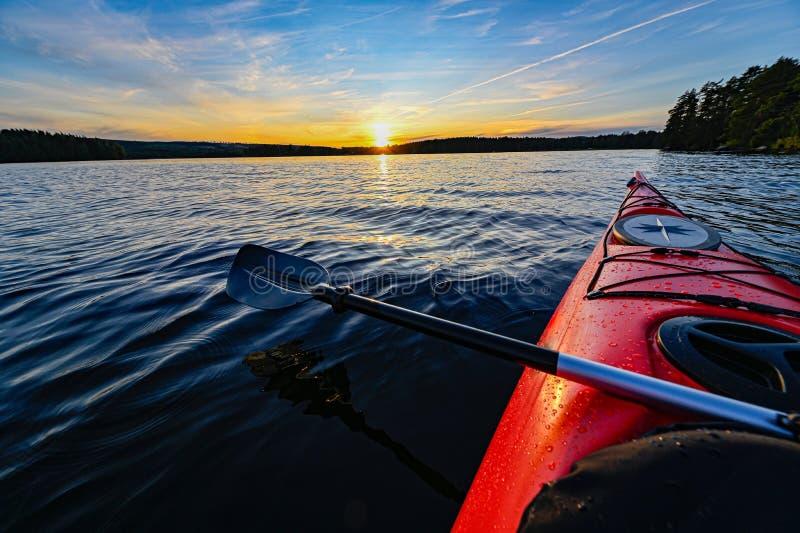 Caiaque plástico vermelho na água calma no por do sol imagem de stock royalty free