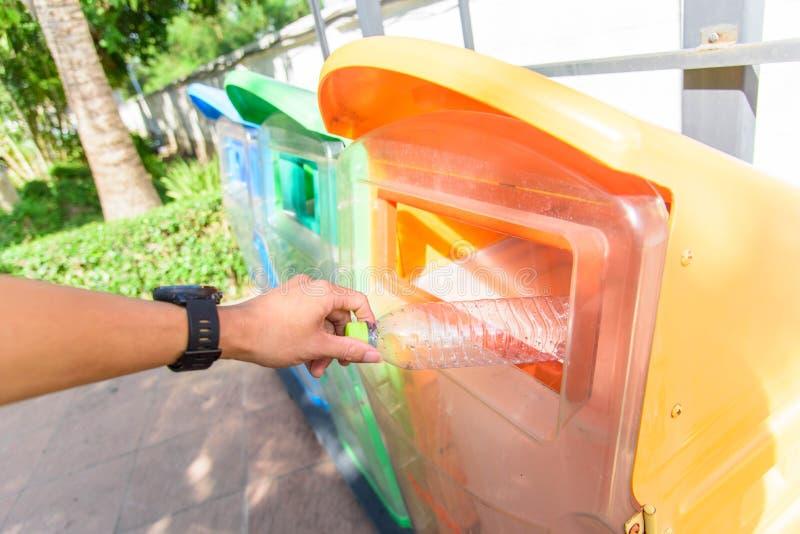 Caiga la botella plástica a trashcan al aire libre imagen de archivo