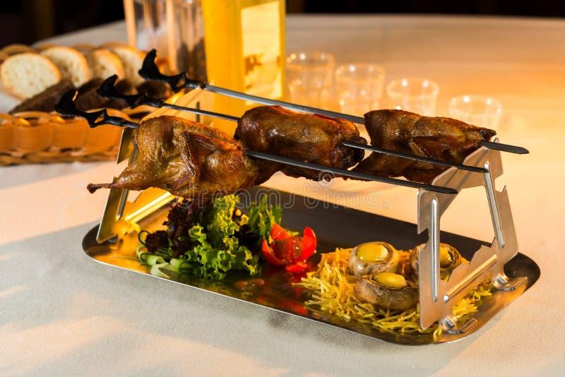 Cailles cuites au four sur une broche photo libre de droits