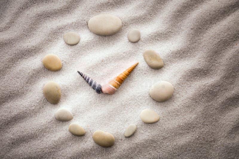 Caillou d'horloge de cadran et flèches stylisés de coquilles sur le sable pour la concentration et la relaxation pour l'harmonie  photos libres de droits