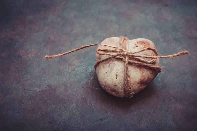 Caillou en forme de coeur de roche attaché avec la ficelle sur le fond en pierre pourpre bleu-foncé, conceptuel, relations, valen photo stock