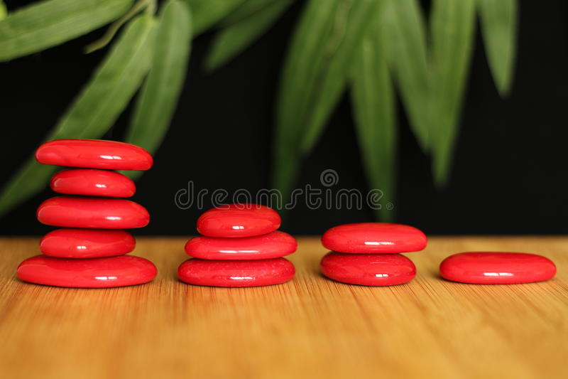 Caillou rouge en pierre étendu sur un plancher en bois et empilé sur plusieurs colonnes dans le mode de vie de zen sur le fond no image stock