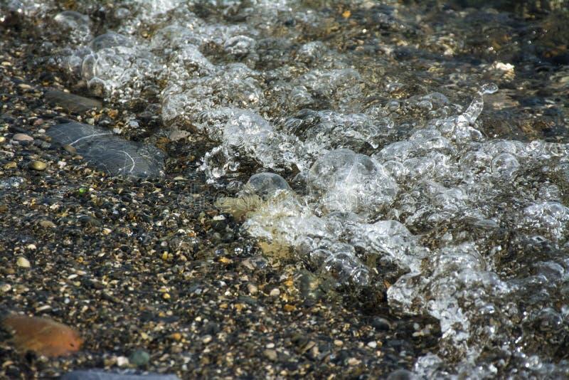 Cailloux colorés dans la vague photo libre de droits