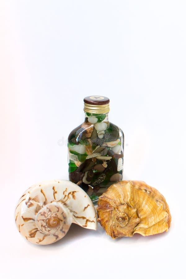 Cailloux dans une bouteille et des coquillages photos libres de droits