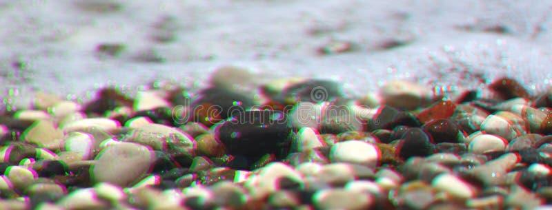 Cailloux de mer avec la vague de mousse sur la plage L'anaglyphe, probl?me a d?cal? l'effet images stock