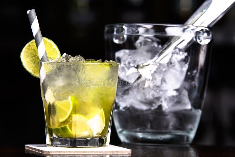 Caipirinha cocktail alongside with bucket full of ice. royalty free stock image