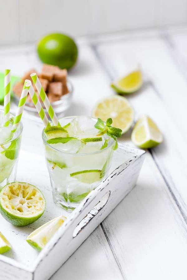 Caipirinha, mojito koktajl z wapnem, liśćmi w pięknych szkłach, brown cukieru, lodowych i nowych, cięcie zielony cytrus na białym obrazy stock