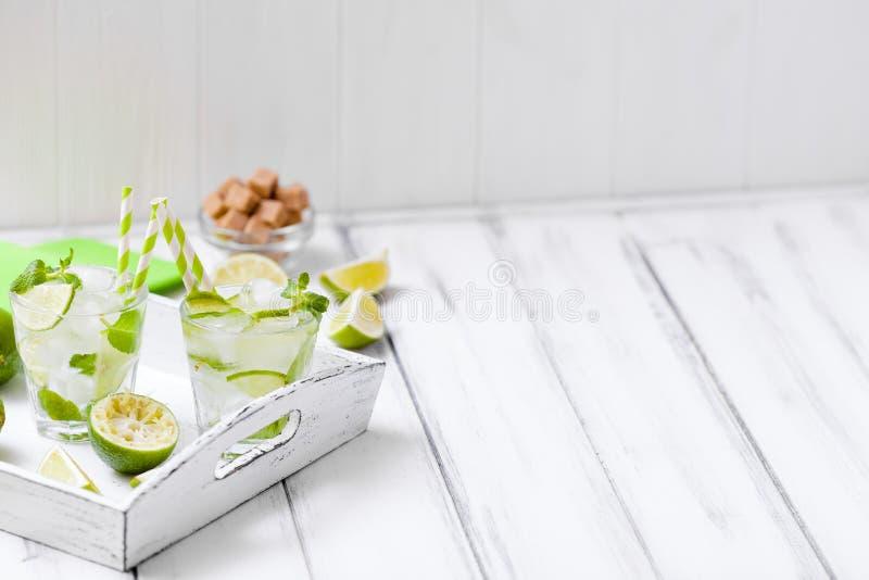 Caipirinha mojitococtail med limefrukt-, farin-, is- och mintkaramellsidor i härliga exponeringsglas, grön citrus för snitt på vi royaltyfria foton