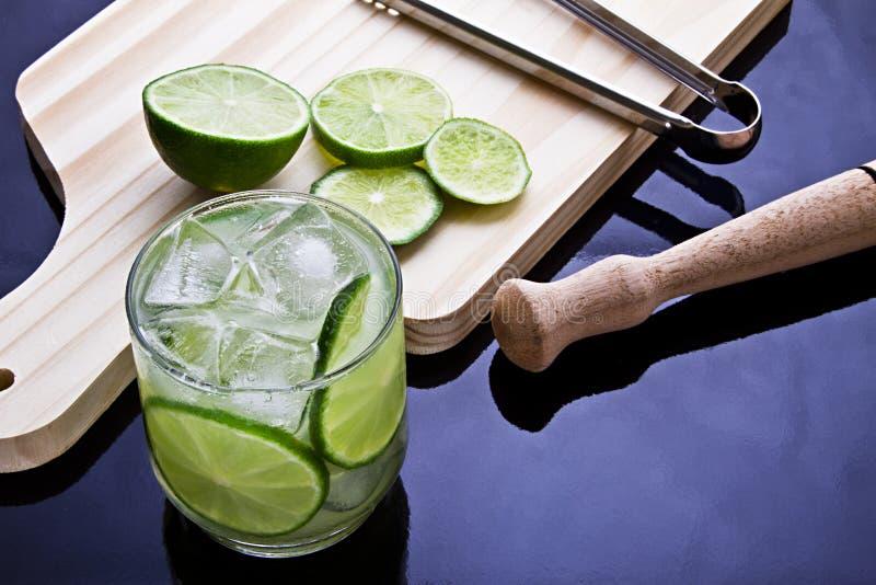 Caipirinha, op citroen-gebaseerde drank, suiker en typisch Braziliaanse cachaça op houten lijst stock fotografie