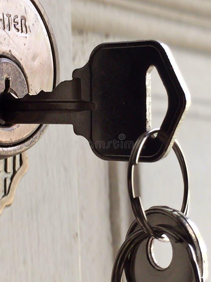 Cair chave na fechadura da porta fotografia de stock