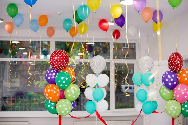 Cair colorido dos balões sob o teto branco fotografia de stock