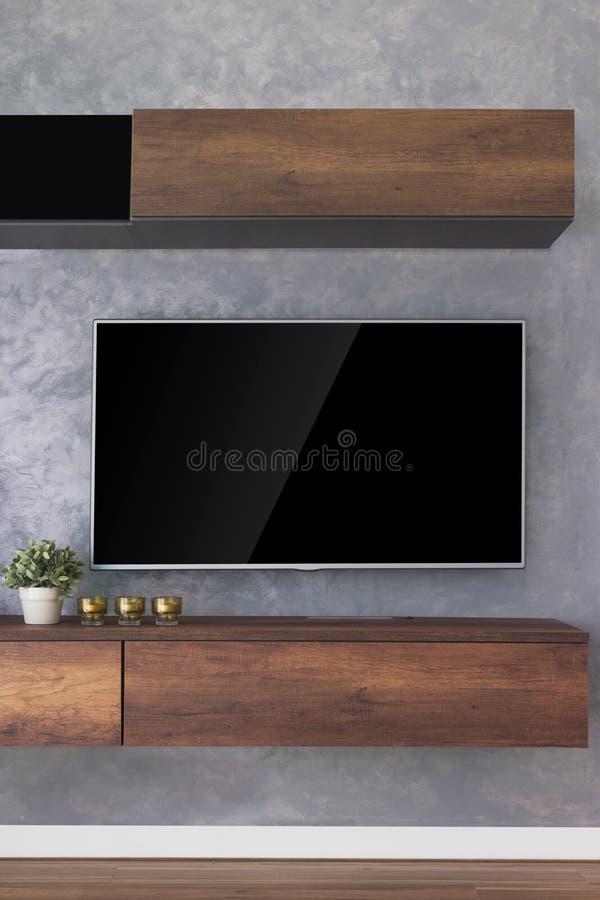 Cair conduzido da tevê na parede do cimento com mobília de madeira do armário e h foto de stock royalty free