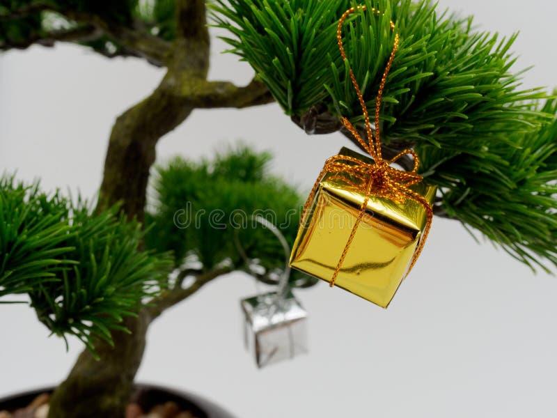 Cair da decoração ou do ornamento do Natal na árvore artificial dos bonsais composta da caixa de presente do ouro e da prata isol imagem de stock