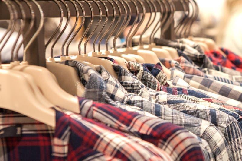 Cair da roupa em uma prateleira Ganchos de pano com camisas Roupa ? moda do ` s dos homens foto de stock