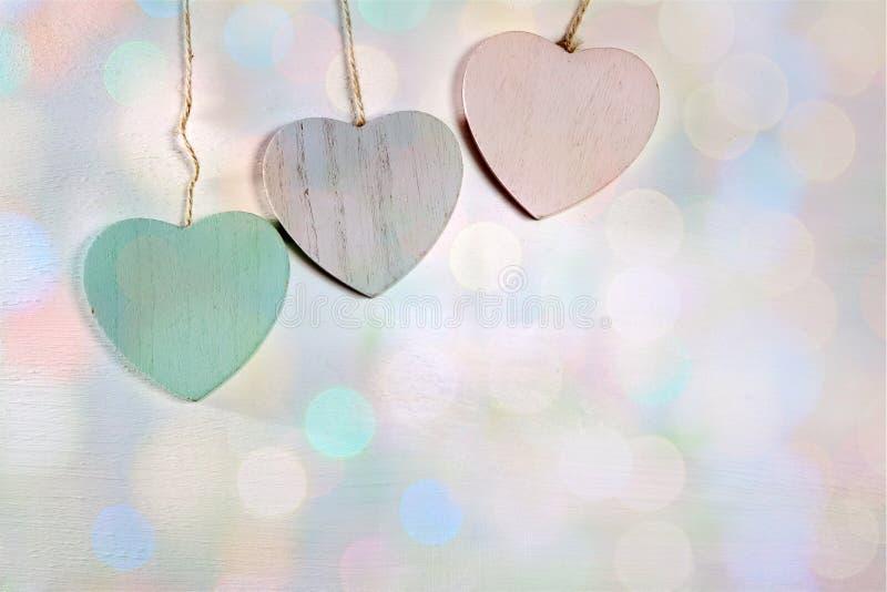Cair de madeira de três corações em uma parede de madeira fotos de stock