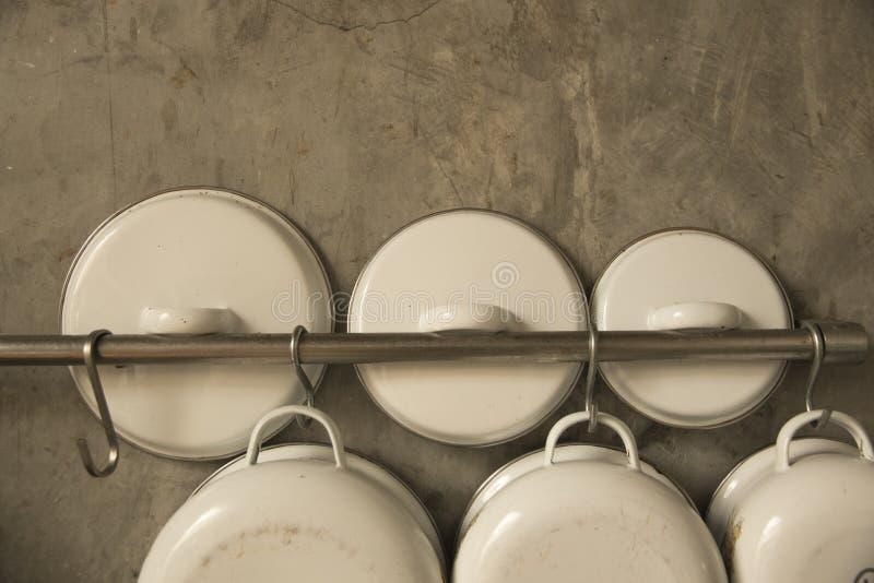 Cair do Kitchenware no fundo da parede do cimento imagem de stock